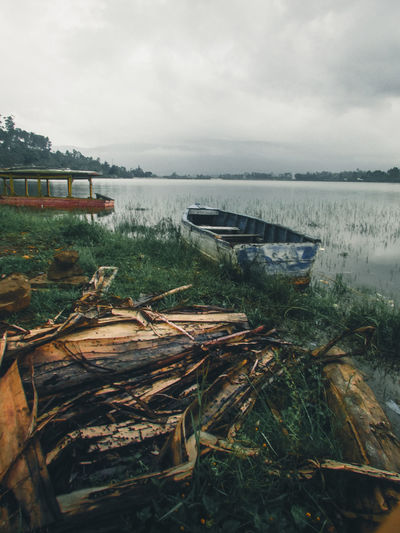 Abandoned boats moored in lake against sky