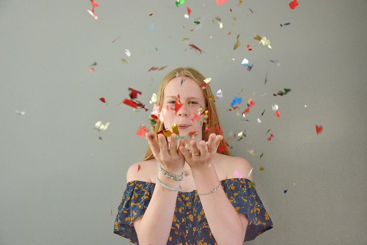Portrait Of Young Woman Blowing Confetti Against Wall