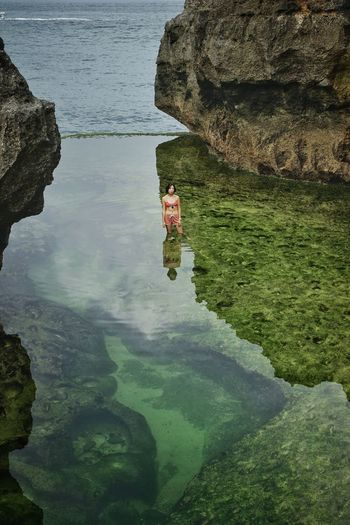 Reflection of woman on rock formation in sea
