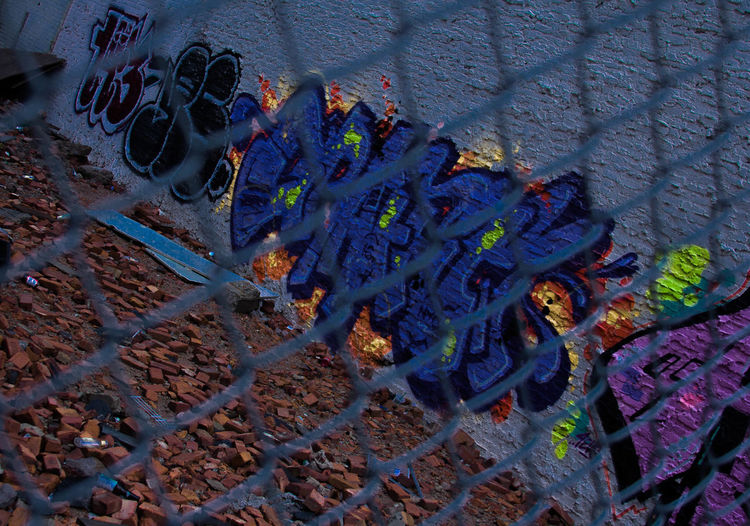 Architecture Chainlink Fence City Cityscape Close-up Day Graffiti No People Outdoors Spraypaint Spraypaint Art Urban Vacant Lot