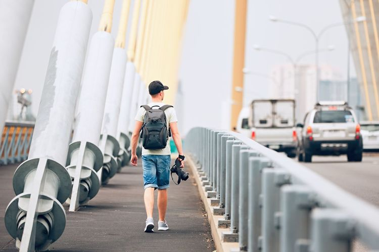 Rear view of young man holding camera while walking on bridge against sky