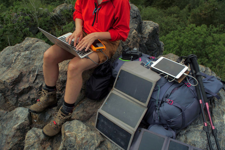 caucasian female hiker sitting on a rock while working on a laptop being charged by solar panels nearby, portable solar charing technology concept Backpacking Camping Charing Cross Freedom Hiking Nature Sitting Solar Panel Tablet Travel Trekking Woman Working Adventure Artist Battery Casual Clothing Communication Connection Day Female Guitar Holding Internet Laptop Leisure Activity Men Music Musical Equipment Musical Instrument Nature Navigation Outdoors People Portable Information Device Real People Sitting Solid String Instrument Technology Uniform Wireless Technology
