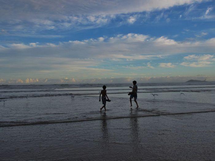 Friends walking at beach against sky