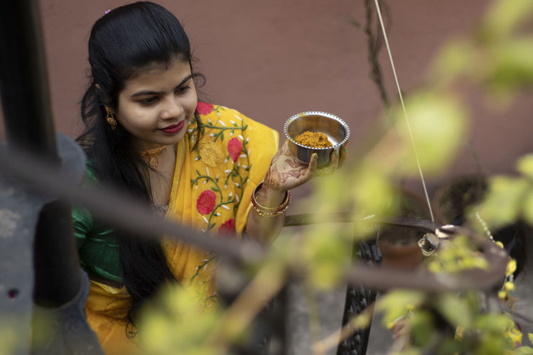 An indian woman in yellow saree is holding a bowl of turmeric paste during indian bengali marriage