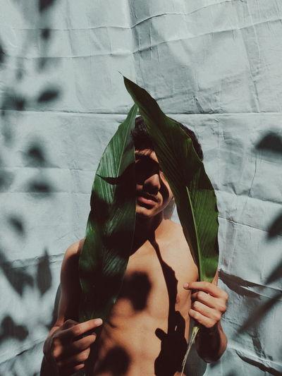 Portrait Of Man Holding Leaf Against Wall