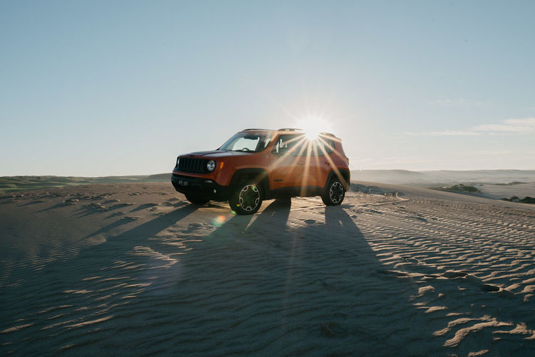 Arid Climate Beauty In Nature Car Clear Sky Climate Day Desert Jeep Land Land Vehicle Landscape Lens Flare Mode Of Transportation Motor Vehicle Nature Non-urban Scene Outdoors Sand Scenics - Nature Sky Sun Sunlight Transportation