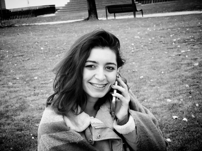 Portrait of smiling young woman talking on mobile phone while standing at park