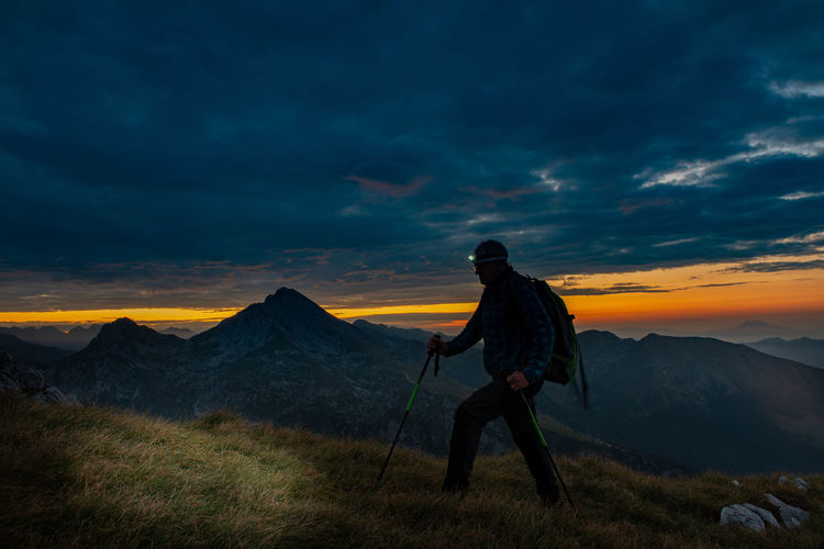 Woman on mountain against sky during sunset