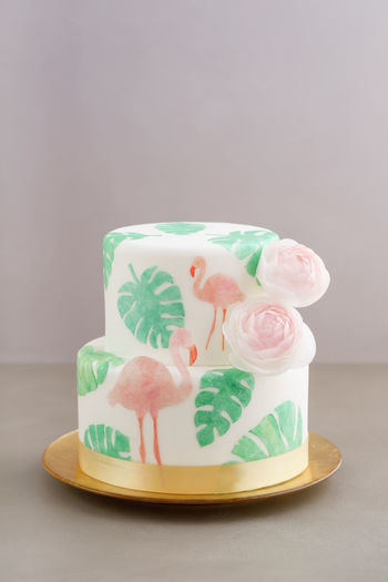 Two tiered tropical wedding cake with fondant, tropical wafer paper leaves and flamingos with ranunculus flowers on golden cale platter Flamingo Cake Tropical Tropical Wedding Cake Wafer Paper Waferpaper Wedding Cake