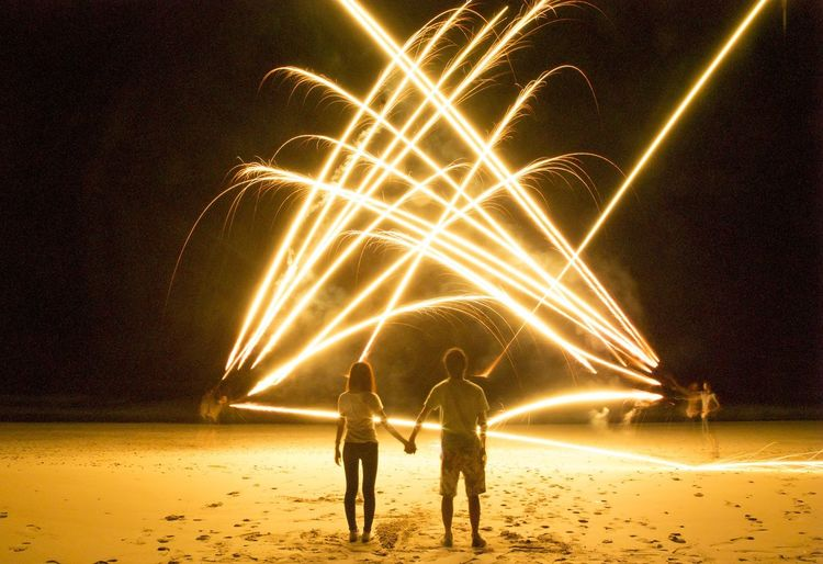 Rear view of man and woman watching light painting on beach at night