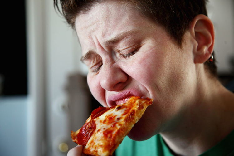 Close-up of mature woman eating pizza
