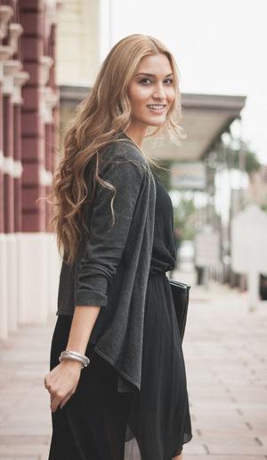Portrait of smiling beautiful woman walking on footpath