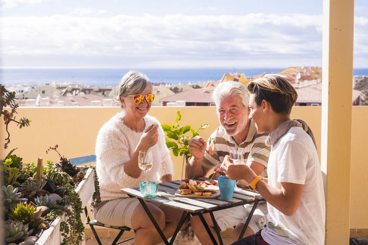 grandmother and grandfather with grandson eating and drinking on terrace looking at the sea Complicity Grandfather Love Adult Day Enjoyment Food And Drink Grandmother Happiness Horizon Over Water Leisure Activity Nature Outdoors People Sea Senior Couple Sitting Sky Smiling Sunglasses Table Togetherness Water Young Boy