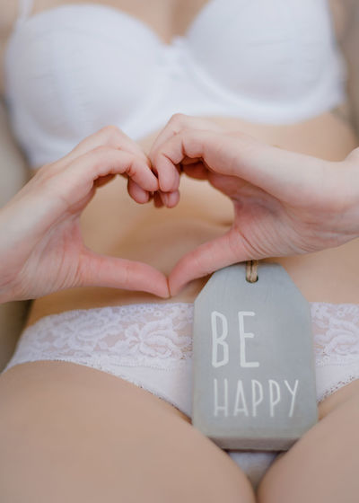 Midsection of sensuous woman making heart shape with hands by be happy tag
