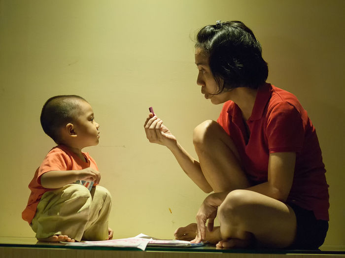 Mother showing crayon to son while sitting on table by wall