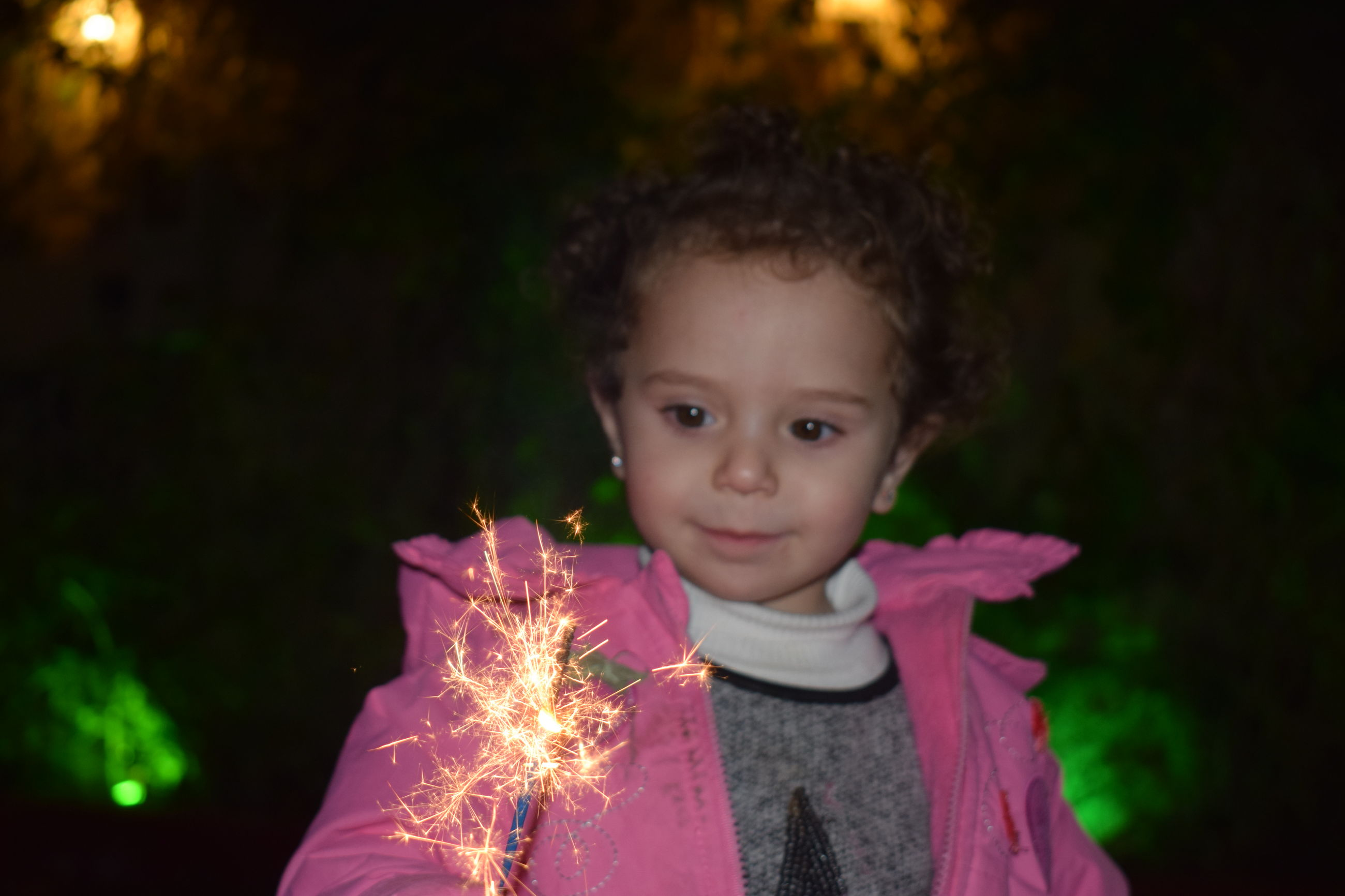 real people, childhood, one person, innocence, looking at camera, portrait, lifestyles, leisure activity, focus on foreground, night, headshot, sparkler, holding, outdoors, close-up, human hand, people