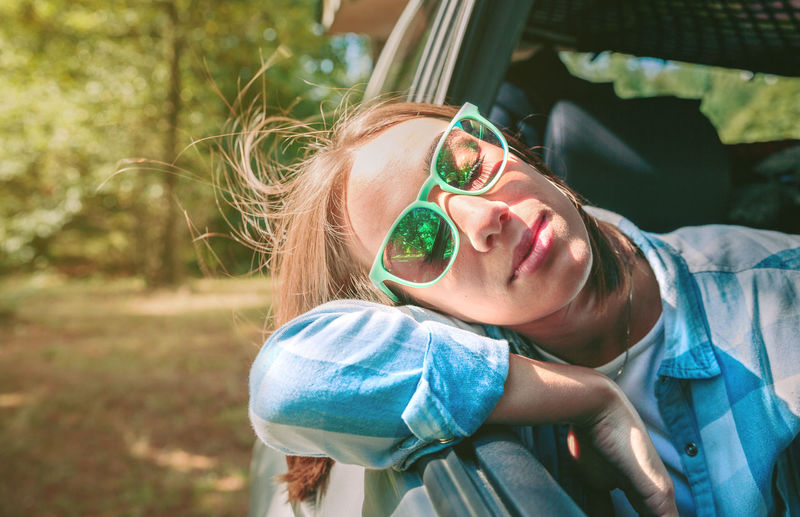Young woman wearing sunglasses traveling in car