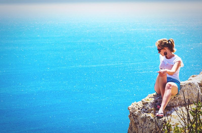 Girl sitting on rock by sea