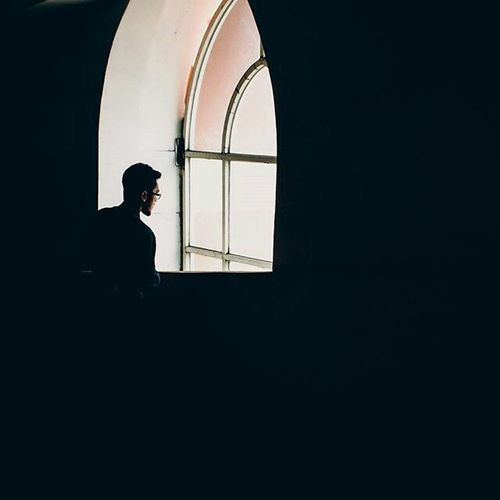 Side view of a silhouette man standing in window