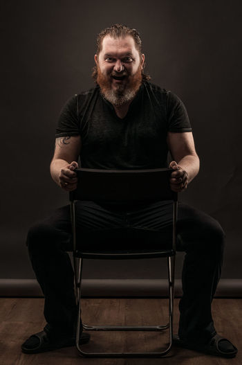 Smiling Mid Adult Man Gesturing While Sitting Against Black Background