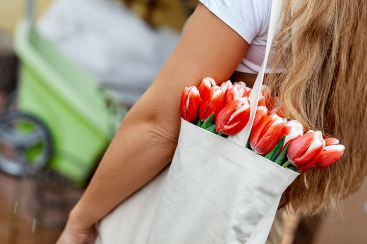 Close-up of a bouquet of tulips in a cloth bag on the shoulder of a girl. gift for women's day,
