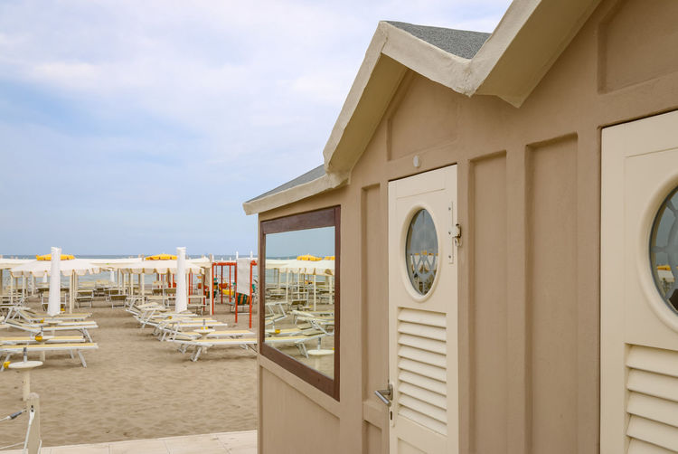 Beige beach cabin on the beach, Italy, Riccione Deck Chair Italy. Riccione Reflection Rimini Vacations Beach Beach Cabins Biege Cabins  Cloud - Sky Day Italy Mirrior No People Outdoors Resort Riccione Sand Sky