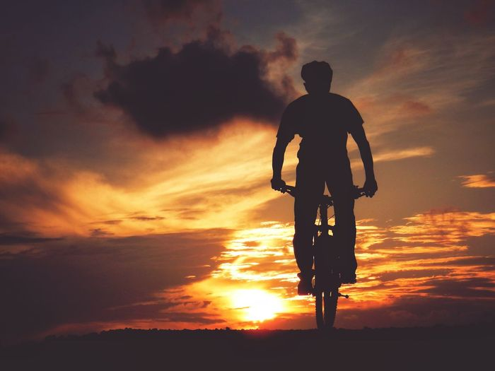 Man cycling against cloudy sky during sunset