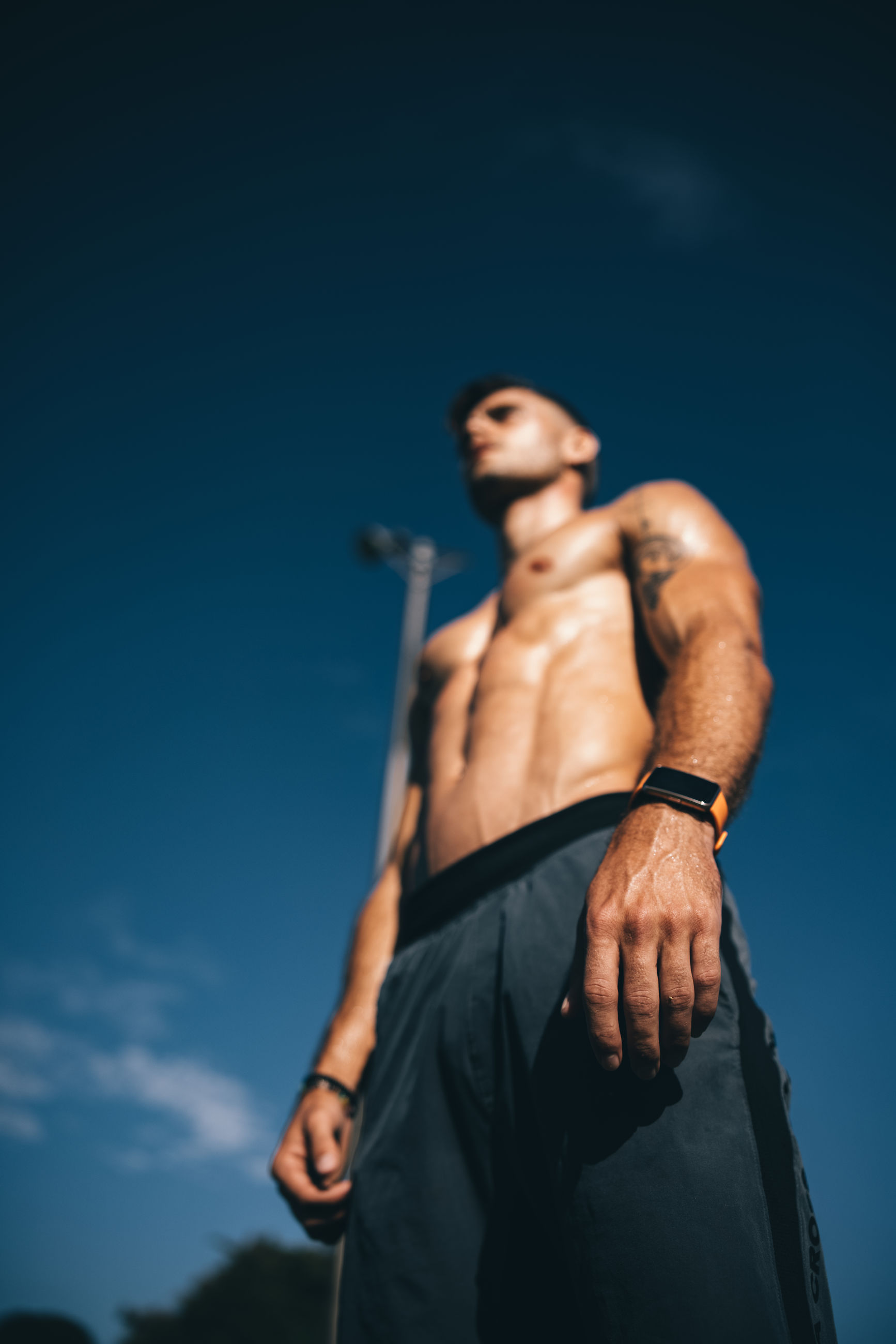 adult, muscular build, men, strength, one person, sports, athlete, exercising, young adult, sky, blue, standing, copy space, lifestyles, sports training, clothing, nature, vitality, low angle view, portrait