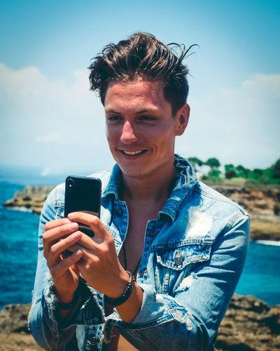 Smiling man using smart phone at beach against sky