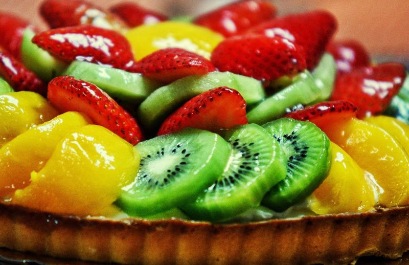 Close-Up Of Fruits On Tart At Table