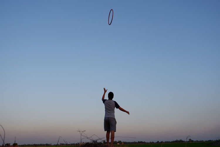 Rear view of man playing plastic hoop against clear sky at sunset