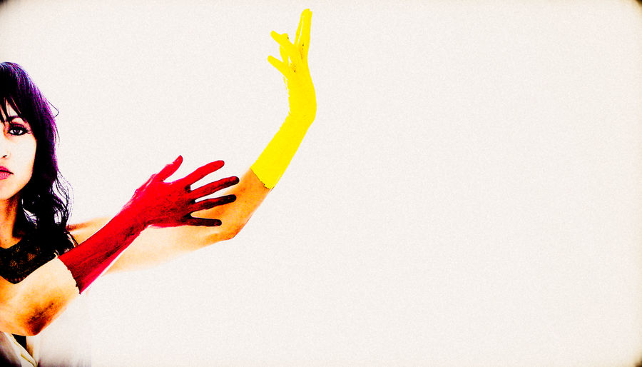 Close-up of woman hand on red wall against white background