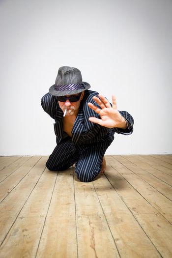 Senior Man Performing Yoga While Smoking Cigarette Against Wall