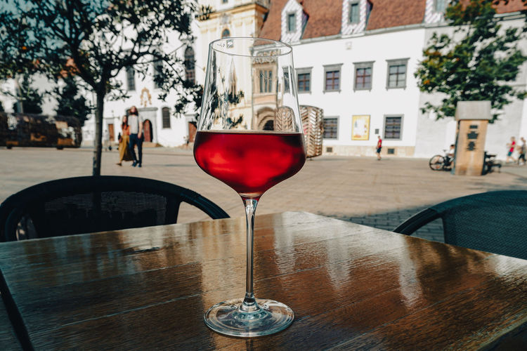 Close-up of wine glass on table in city