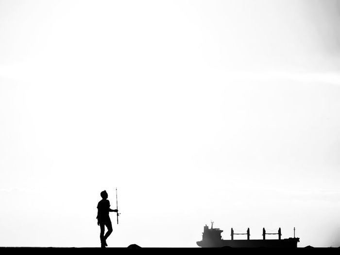 Silhouette man standing against clear sky