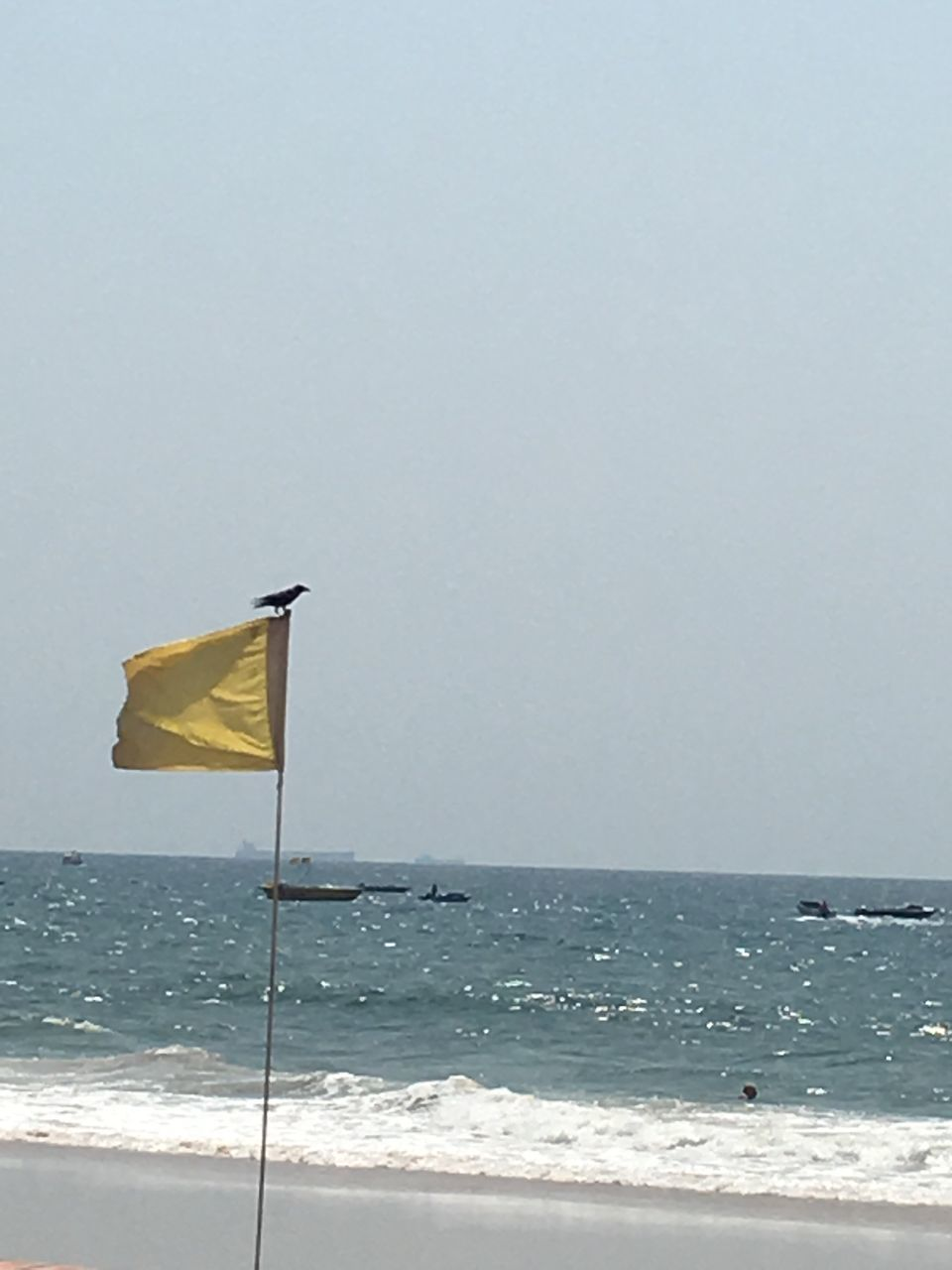 sea, flag, horizon over water, water, beauty in nature, scenics, nature, yellow, beach, clear sky, day, outdoors, no people, tranquility, sky