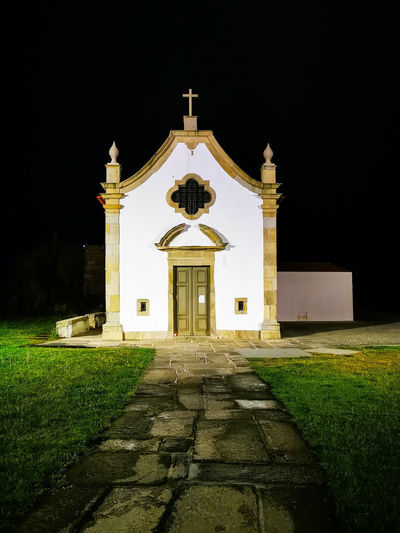 Church by building against sky at night