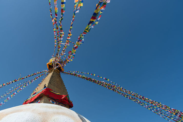 Boudha stupa, at kathmandu city in nepal against blue sky, with religious colorful flags waving.
