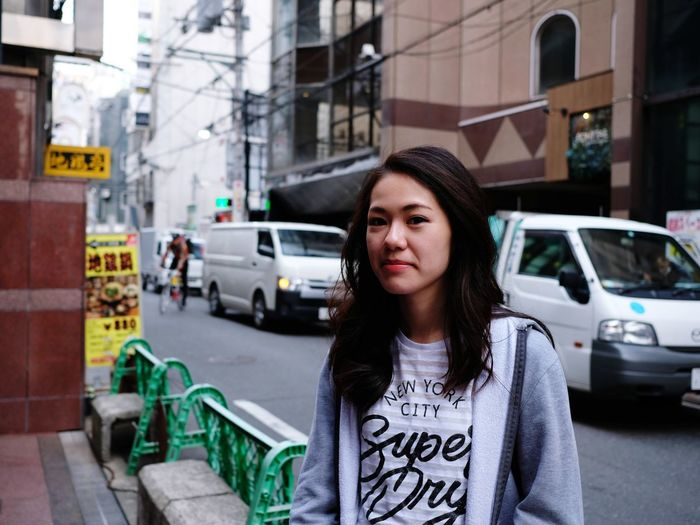 Beautiful young woman standing on street in city