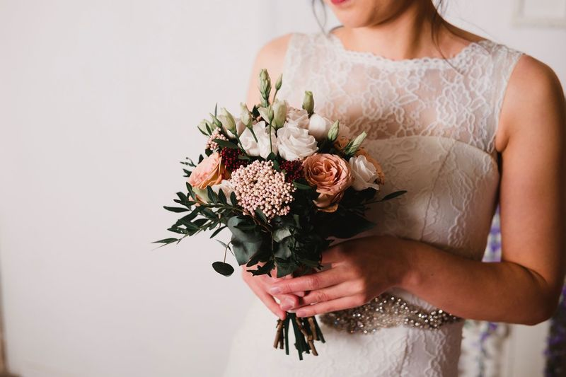 Midsection of bride holding flower bouquet against wall