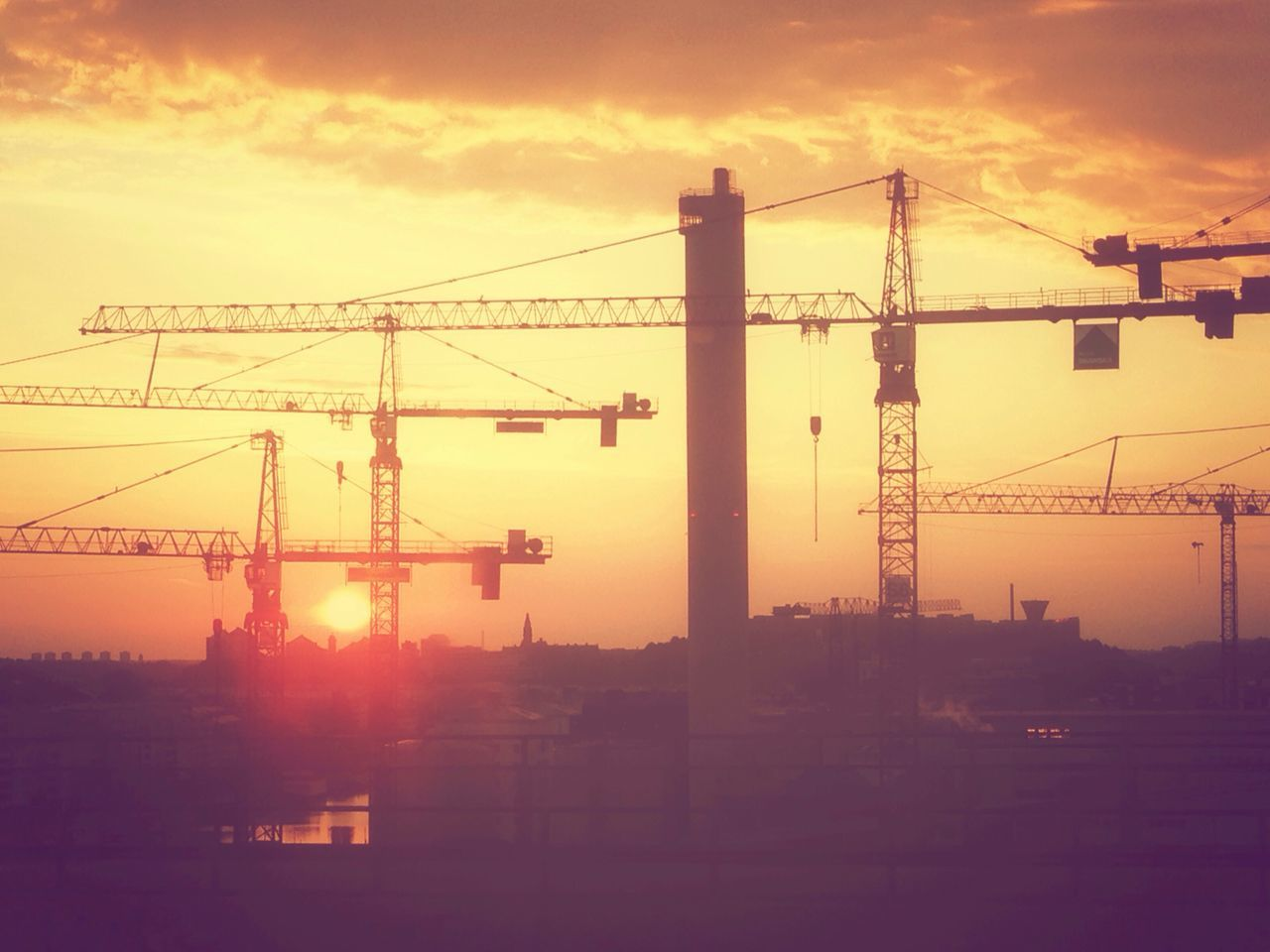 Low Angle View Of Silhouette Cranes Against Sky During Sunset
