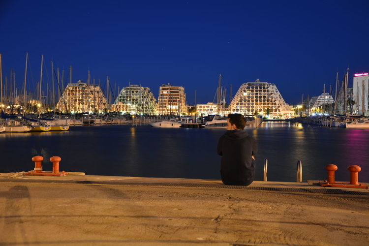 Rear View Of Man Sitting On Pier At Harbor Against Clear Blue Sky At Dusk