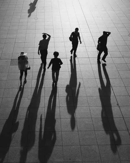 High Angle View Of People Walking With Long Shadows On Footpath In City