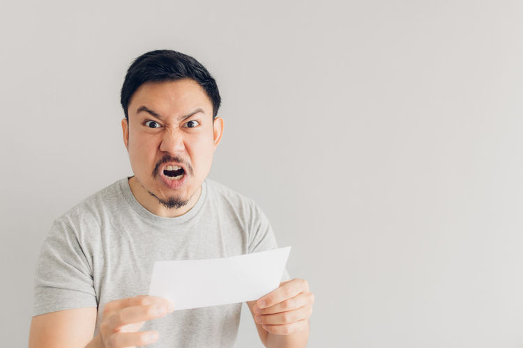 Portrait of young man holding paper against white background