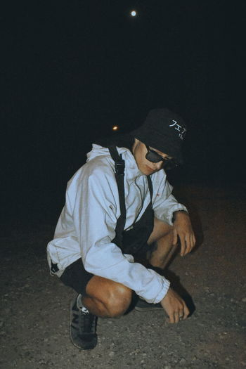 Full length of young man sitting in park at night