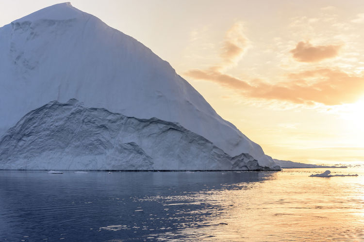 Sunset time on Icebergs in Arctic Ocean in Greenland Capture Tomorrow Water Sky Beauty In Nature Scenics - Nature Waterfront Sea Sunset Tranquil Scene Mountain Cloud - Sky Tranquility Cold Temperature Nature Idyllic Non-urban Scene Ice No People Snow Winter Outdoors Iceberg Snowcapped Mountain