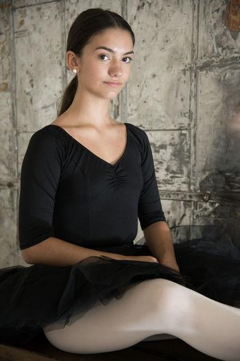 Portrait of ballerina against wall