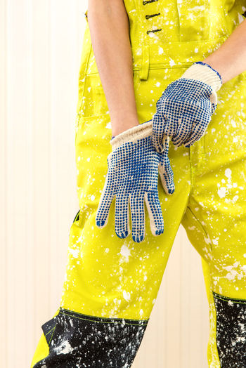 Cropped Image Of Woman In Dirty Coveralls Wearing Gloves Paintbrush While Standing Against Wall
