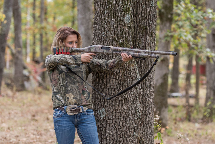 Young Woman Holding Gun While Standing By Tree Trunk At Forest