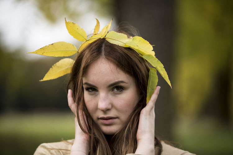 Close-up portrait of young woman holding leaf crown
